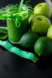 Frullato verde vicino al centimetro ed ingredienti per su fondo di legno nero Dieta detox Bevanda sana Fotografie Stock Libere da Diritti