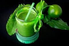 Frullato verde vicino al centimetro ed ingredienti per su fondo di legno nero Dieta detox Bevanda sana Fotografie Stock