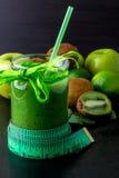 Frullato verde vicino al centimetro ed ingredienti per su fondo di legno nero Dieta detox Bevanda sana Fotografia Stock
