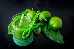 Frullato verde vicino al centimetro ed ingredienti per su fondo di legno nero Dieta detox Bevanda sana Immagine Stock Libera da Diritti