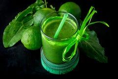 Frullato verde vicino al centimetro ed ingredienti per su fondo di legno nero Dieta detox Bevanda sana Immagine Stock