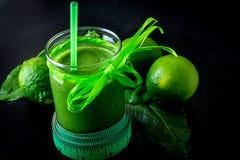 Frullato verde vicino al centimetro ed ingredienti per su fondo di legno nero Dieta detox Bevanda sana Alimento puro Fotografia Stock