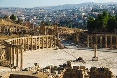 Fórum oval e cidade greco-romana antiga colonnaded longa Gerasa da rua ou do cardo Jerash moderno no fundo Indústria do turismo,  Imagens de Stock