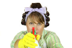 Frumpy Housewife Takes Aim. Frumpy housewife takes deadly aim with the spray bottle Royalty Free Stock Images