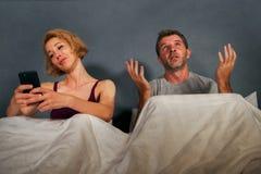 Frun som använder mobiltelefonen i säng med hennes ilskna frustrerade make och mankänslan, ignorerade upprivet, och borrat i kvin arkivfoto