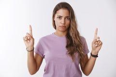 Frustated разочаровало привлекательную смущенную девушку поднимая указательные пальцы указывая вверх по выглядеть не поддавшийся  стоковые изображения rf