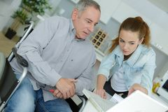 Frustated man on wheelchair with laptop and carer helping Royalty Free Stock Photography