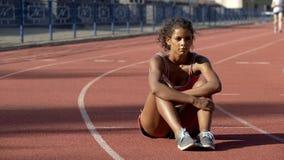 Frustré avec la séance isolée de sportive biracial de résultats au milieu de la voie photographie stock
