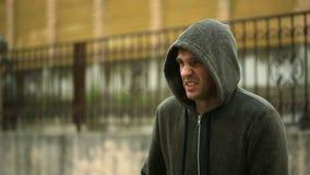 Frustré par le temps, se tenant sous la pluie L'homme fâcheux banque de vidéos