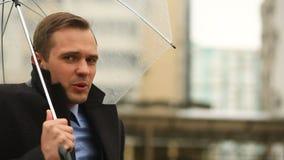 Frustrado pelo tempo, estando sob o guarda-chuva durante a chuva Homem infeliz em um terno video estoque