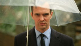 Frustrado pelo tempo, estando sob o guarda-chuva durante a chuva Homem infeliz em um terno filme