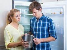 Frustraited使挨饿的女性和人在冰箱附近没有任何食物 库存照片