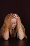 Frustrated. Sitting woman with long blond hair and hands on head royalty free stock photos