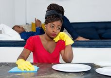 Frustrated african american woman cleaning room with lazy man stock image