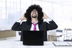 Frustrated African businessman with a laptop Stock Images