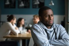Frustrated african man suffers from racial discrimination alone. Frustrated excluded outstand african american men suffers from bullying or racial discrimination stock image