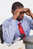 Frustrated Afro businessman with head in hands at desk Royalty Free Stock Image