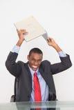 Frustrated Afro businessman smashing laptop on desk Stock Photography