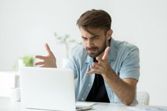 Angry man disagree with fake online news looking at laptop. Frustrated angry entrepreneur outraged by laptop problem, furious mad man using computer looking at Stock Photos
