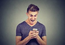 Frustrated angry man reading a text message on smartphone screaming Stock Image