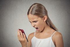Frustrated angry teenager girl yelling while on phone Stock Images
