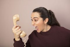 Frustrated woman screaming at the telephone. Frustrated angry woman screaming at the telephone as she grips a corded land line instrument in her hand Stock Image