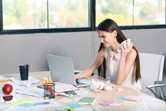 A frustrated girl is working behind a laptop and crumpling paper documents. Inside the office. royalty free stock images
