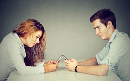 Frustrated annoyed young woman and man sitting at table with smartphone Royalty Free Stock Photography