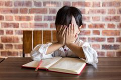 Frustrated Asian chinese little girl doing homework. At home Stock Images