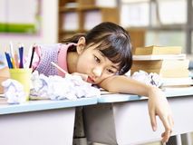 Frustrated asian elementary school girl. Asian elementary school girl frustrated after several failed attempts while writing an essay royalty free stock photo
