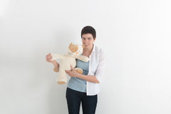 Frustrated attractive young woman biting a plush toy or teddy bear with a snarl and frown of anger stock image