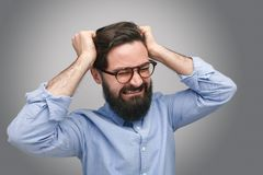 Frustrated bearded man in glasses. Frustrated and upset bearded man in glasses holding head on gray background Stock Image