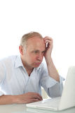 Frustrated bemused man with laptop Stock Images