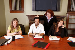 Frustrated boss ignored. Employees busy on cell phones, boss is upset stock images