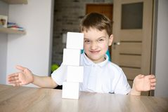 Frustrated boy destroying brick tower he built. Stock Photography