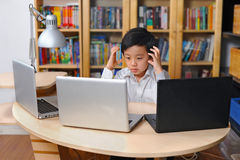 Frustrated boy in white shirt in front of multiple laptop Royalty Free Stock Photo
