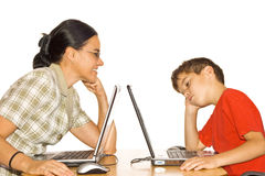 Frustrated boy working on a laptop computer. Small boy gives up on the laptop and holds his head in his hand in despair royalty free stock photography