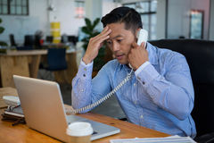 Frustrated business executive talking on telephone. In office Royalty Free Stock Photo