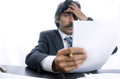 Frustrated Business Man. A frustrated man holding his head at his desk Royalty Free Stock Photos