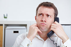 Frustrated business man on. The phone in waiting queue Royalty Free Stock Images