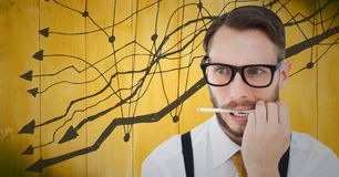 Frustrated business man with pen in mouth against yellow wood panel and graph. Digital composite of Frustrated business man with pen in mouth against yellow wood Stock Photo