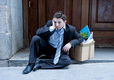 Frustrated business man on street fired with cardboard box Royalty Free Stock Photography