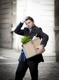 Frustrated business man on street fired carrying cardboard box Stock Photos