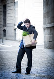 Frustrated business man on street fired carrying cardboard box. Frustrated business man fired in crisis carrying cardboard box on street Royalty Free Stock Photo