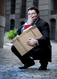 Frustrated business man on street fired carrying cardboard box. Frustrated business man fired in crisis carrying cardboard box on street Stock Image