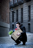 Frustrated business man on street fired carrying cardboard box Royalty Free Stock Photos