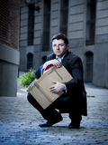 Frustrated business man on street fired carrying cardboard box. Frustrated business man fired in crisis carrying cardboard box on street Royalty Free Stock Photography