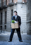 Frustrated business man on street fired carrying cardboard box Royalty Free Stock Image