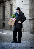 Frustrated business man on street fired carrying cardboard box Stock Images