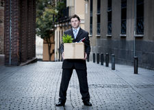 Frustrated business man on street fired carrying cardboard box. Frustrated business man fired in crisis carrying cardboard box on street Royalty Free Stock Photos